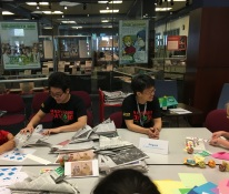 The Curator of the Prange Collection and a student assistant help visitors make a samurai hat (kabuto) out of newspaper.