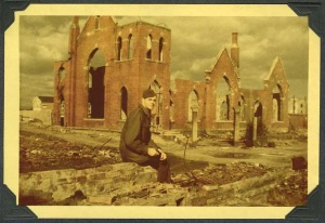 Emerson Chapin in uniform in Osaka, Japan sitting amongst ruins in front of a destroyed building of which only the outside walls remain.